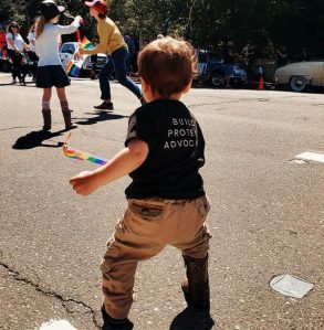 Toddler playing with a rainbow pride flag at an LGBTQIA+ community event, wearing a black North Bay LGBTQI Famililes T-shirt that says Build, Protect, Advocate on the back.