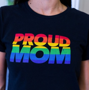 The front of an LGBTQIA+ parent's black t-shirt that says Proud Mom in rainbow striped text.